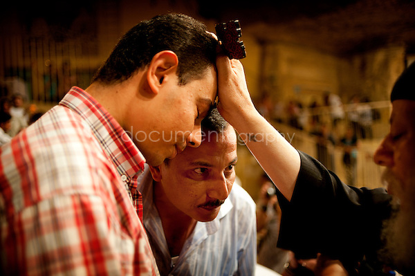 Father Samaan blesses two men amongst hundreds of devoted Copts who came to the Thursday sermon in the St Simeon Church in Mokattam.<br />