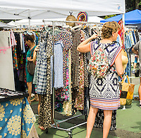 Shoppers at the original Brooklyn Flea in the neighborhood of Clinton Hill on Saturday, August 8, 2015. The flea market, which hosts over 100 booths by Brooklyn vendors offering handmade or used merchandise opens up in the athletic field of Bishop Loughlin High School on Saturdays. Shoppers come from all over the city for the bargains and one-of-a-kind local merchandise that is offered for sale.  (© Richard B. Levine)