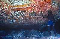 Deep in Arnhem Land an Australian Aboriginal explaining a remote located cave painting to me. Northern Territory, Australia