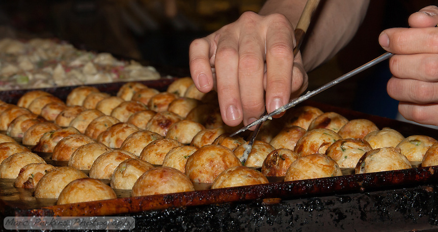 Chef Ryota Akai of Japan turns takoyaki during a demonstration of takoyaki cooking at Mitsuwa Market in Costa Mesa, California.  The chef used chopsticks to delicately poke and turn each takoyaki ball, and here he's preparing to turn a ball at the front of the pan.