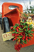 An old red truck pickup truck is loaded with chile ristras along with squash, corn and other harvest bounty at a fruit stand in Velarde, New Mexico, during the harvest season in September