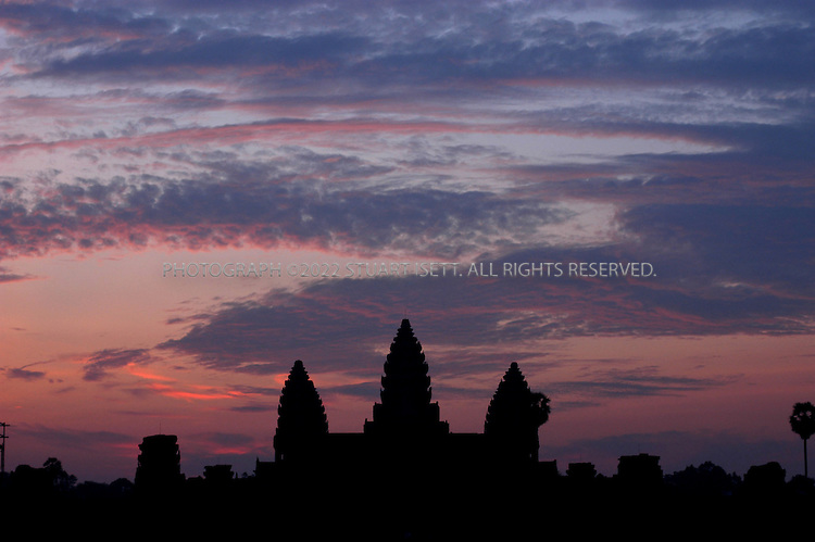 """4/20/2003--Angkor Wat Temples, Siem Reap, Cambodia..Angkor Wat at sunrise. Angkor Wat is located about six kilometers (four miles) north of Siem Reap, south of Angkor Thom. ..Angkor Wat was built in the first half of the 12th century (113-5BC). Estimated construction time of the temple is 30 years by King Suryavarman II, dedicated to Vishnu (Hindu), replica of Angkor Thom style of art...BACKGROUND .Angkor Wat, the largest monument of the Angkor group and the best preserved, is an architectural masterpiece. Its perfection in composition, balance, proportions, relief's and sculpture make it one of the finest monuments in the world. ..Wat is the Thai name for temple (the French spelling is """"vat """"), which was probably added to """"Angkor """"when it became a Theravada Buddhist monument, most likely in the sixteenth century (for the etymology of the name 'Angkor' see page 17) After 1432 when the capital moved to Phnom Penh, Angkor Wat was cared for by Buddhist monks. ..It is generally accepted that Angkor Wat was a funerary temple for King Suryavarman II and oriented to the west to conform to the symbolism between the setting sun and death. The bas-reliefs, designed for viewing from left to right in the order of Hindu funereal ritual, support this function. ...All photographs ©2003 Stuart Isett.All rights reserved.This image may not be reproduced without expressed written permission from Stuart Isett."""
