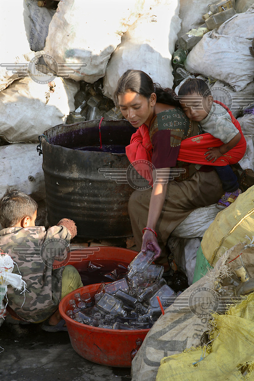 Woman with two young children washing bottles at a glass recycling business.