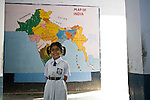 A young girl child in her school uniform standing against the map of India, smiling into the camera. Photograph &copy; Santosh Verma