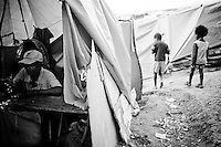 A man uses a sewing machine in his tent in a camp for those displaced by the recent earthquake in Petionville, outside Port-au-Prince, Haiti.