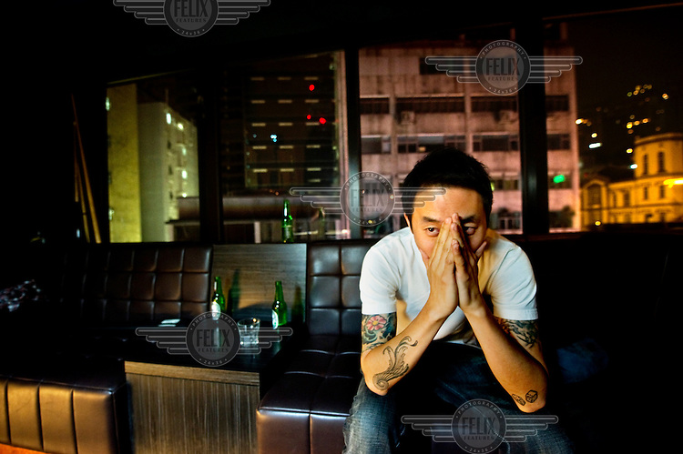 A man at a nightclub sits with his head in his hands.