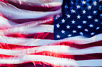 A double exposure abstract image of a waving American Flag.