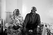 Asmara, Eritrea.November 2002.Birhan Aim Hospital  (Light to the Eye Hospital)..A wife visits her husband who is blind in one eye and has had surgery in the other. It is all smiles as the operation was successful but this patient will need to wear glasses.