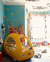 A buttercup-yellow plastic car serves as a bed in the corner of a bright and cheerful boy's bedroom