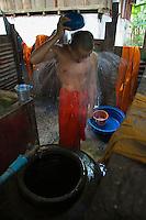 Monk taken a shower at a Monastery near Vientiane, Laos