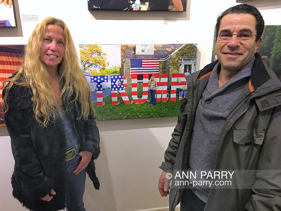 """Huntington, New York, USA. March 5, 2017. Eileen Fuscaldo and her husband, next to 2016 photo of Eileen, at Opening Reception for """"Her Story Through Art"""" Invitational Art Show, celebrating Women's History Month, at Huntington Arts Council, Main Street Gallery. Artists Tara Leale Porter, Irene Vitale, Anahi DeCanio, Ann Parry, Show March 2 - 25, 2017."""