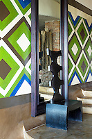 A black wood chair at Singita Pamushana Lodge, Malilongwe Trust, Zimbabwe, in front of a mirror and walls painted in a blue and green pattern