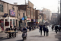 Uighurs walk past businesses in the Old Town section of Kashgar, Xinjiang, China.