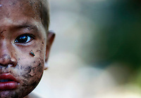 A fly lands on the face of an illegal immigrant child from Myanmar at a rubbish dump site near Mae Sot December 22, 2009. Despite terrible living condition and the fear from being sent back to their country, several hundred illegal immigrants from Myanmar live and earn an average of one US dollar per day collecting plastic at the rubbish dump near the border town of Mae Sot. Myanmar's long standing political crisis has forced millions of people to cross the border for a better and safer life. The first refugees arrived and set up camps in the Myanmar-Thailand border in 1984. Now, there are over 140,000 refugees in nine official camps along Thailand's western border. Many more are expected to be in unofficial settlements.  REUTERS/Damir Sagolj  (THAILAND)