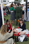 Goodwood Festival of Speed. Goodwood Sussex UK. Women wearing retro clothes gossip together.