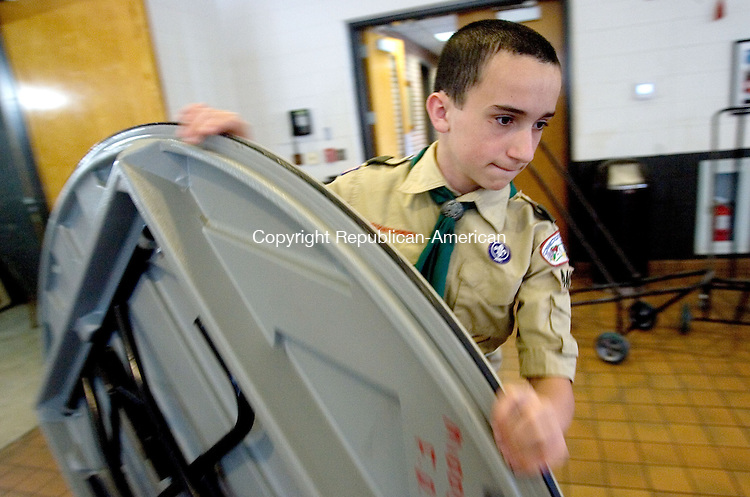 MIDDLEBURY CT. 03 May 2015-050315SV09-Bob Holmes, 14, of Middlebury rolls out a table while setting up for the Boy Scout Troop 444 Pasta dinner at the firehouse in Middlebury. The fundraiser serves about 300 dinners and the proceeds pay for their camping trips and expenses through out the year. <br /> Steven Valenti Republican-American