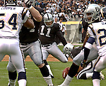 Oakland Raiders punter Shane Lechler (9) holds for kicker Sebastian Janikowski (11) to make field goal on Sunday, September 28, 2003, in Oakland, California. The Raiders defeated the Chargers 34-31 in overtime.
