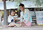 A woman helps her daughter with homework in the Cambodian village of Bour.