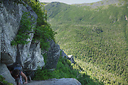 A hiker climbs a steep, exposed, rocky section of Six Husbands Trail in the White Mountains of New Hampshire during the summer months.