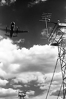 A prop plane takes off on a cloudy day.  Communication towers are on the periphery of the image.