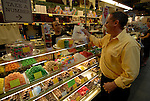 Reading Terminal Market, man buying candy, mod rel..Philadelphia, Pennsylvania, PA USA.  Photo copyright Lee Foster, 510-549-2202, lee@fostertravel.com, www.fostertravel.com.  Photo 237-30562