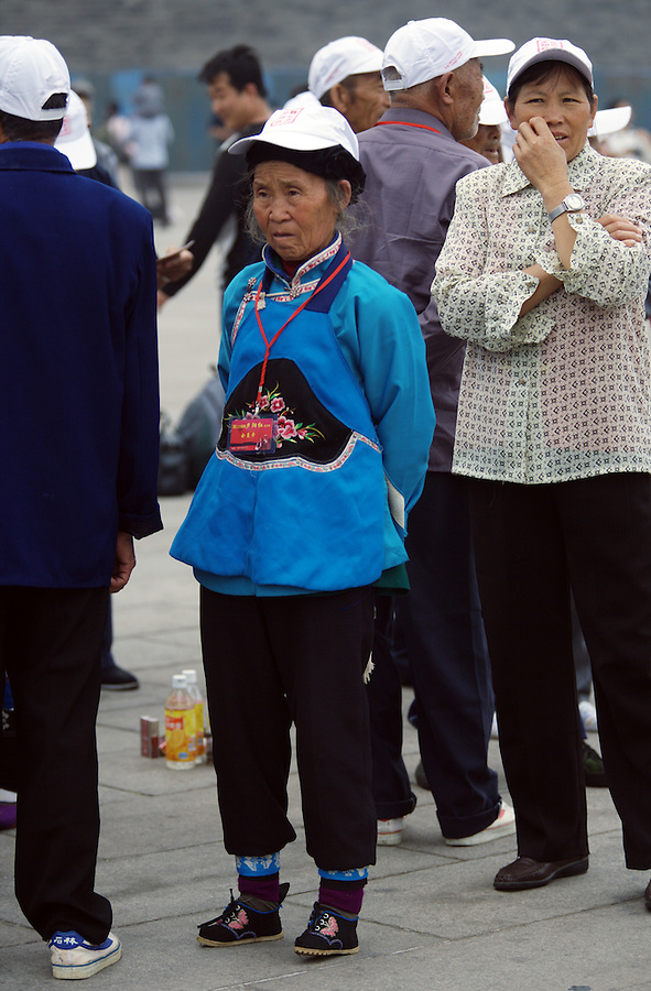 A woman with bound feet from Yunnan Province visits Tiananmen Square in Beijing. Foot binding, an attempt to halt the growth of the feet, began late in the Tang Dynasty and spread through the overwhelming majority of the Chinese population until it was finally outlawed in the 1911 Revolution of Sun Yat-Sen.