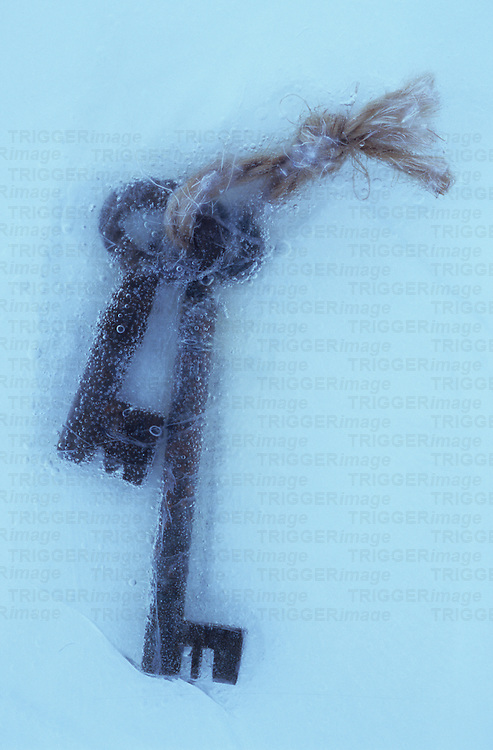 Two rusty deadlock vintage keys tied together with string in sheet of ice