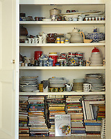 Cookery books share a closet with a collection of china, pottery and whimsical kitchenware