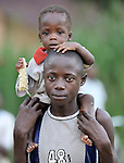 A boy carries his little brother in the Congolese village of Wembo Nyama..