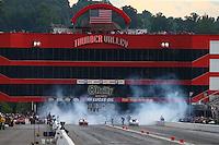 Jun 20, 2015; Bristol, TN, USA; Overall view as NHRA pro stock driver Greg Anderson (left) burns out alongside Chris McGaha during qualifying for the Thunder Valley Nationals at Bristol Dragway. Mandatory Credit: Mark J. Rebilas-