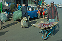 28/01/12. Addis Ababa, Ethiopia. A man pushes his wares of fruit, in a wheelbarrow, through the Mercato, Addis. In the Mercato, it is possible to buy everything from computers to livestock, scrap metal to recycled plastic containers. Nothing appears to go to waste or to not have a value. Photo credit: Jane Hobson.