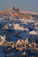 Goreme, Nevsehir, Cappadocia, Turkey. Hot air Balloons fly over the village of Goreme, with uchisar in the background. A fresh pack of snow has turned the winter landscape of Goreme National Park into an even bigger fairy tale. Photo by Frits Meyst / MeystPhoto.com