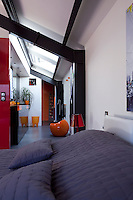 In the bedroom a long space lined with built-in cupboards leads to the shower room and is lit by a series of skylights