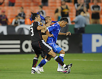 El Salvador National Team forward Mark Lester Blanco (12) shields the ball against DC United defender Juan Manuel Pena (3) while in the back ground a fan jump into the field during the game.  DC United defeated El Salvador National Team 1-0 in a international charity match at RFK Stadium, Saturday June 19, 2010.