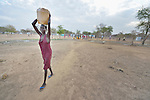 A woman carries water in an internally displaced persons camp in Manangui, South Sudan. Families started arriving here shortly after fighting broke out in December 2013, and new families continued to arrive in March 2014 as fighting continued. Many are living in the open and under trees. The ACT Alliance is providing the displaced families and the host communities affected by their presence with a variety of support.