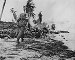 "July 21, 1944 - Invading Marines ""hug the deck"" on the beaches of Guam as Japanese land mines stopped some of theri tanks and sniper fire forced them to keep their heads down."