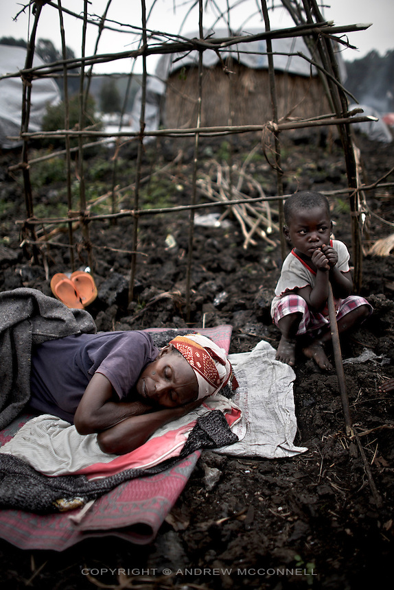 A mother and child, displaced by the conflict, rest in Mugunga 1 IDP site, home to some 10,000 people, in Goma, North Kivu, DRC, on Friday, Feb. 22, 2008..