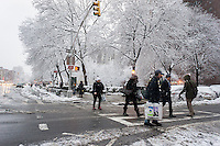 Passer-by hurry home past trees laden with heavy wet snow in the Chelsea neighborhood of New York on Monday, February 3, 2014. A winter storm with wet, slushy snow hit the city with an expected snowfall of 4 to 8 inches. (© Richard B. Levine)