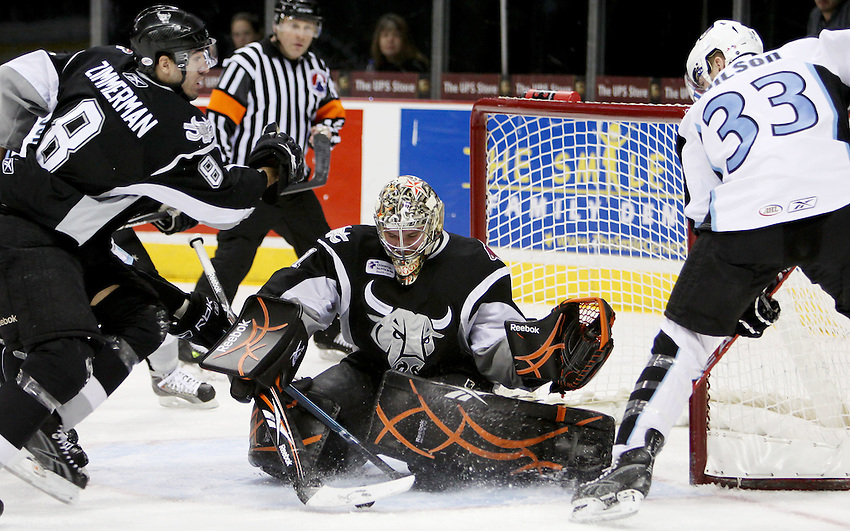 San Antonio goaltender Justin Pogge, center, and teammate Sean Zimmerman, left, defend the net against Milwaukee's Colin Wilson during the first period of an AHL hockey game between the Milwaukee Admirals and the San Antonio Rampage, Sunday, Jan. 24, 2010, at the AT&T Center in San Antonio. (Darren Abate/pressphotointl.com)