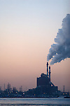 A power plant along the shore of Lake Michigan emits smoke into the late evening sky on a cold winter day.