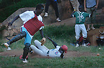 Jawingo looks for the ball as another player slides safely into home, scoring a run at a baseball game at Nsambya, Wednesday March 17, 2004. A small group of local enthusiast meets once a week to practice and play the game With football (soccer) the ruling sport, baseball enjoys a small, but loyal following. (Rick D'Elia)<br />