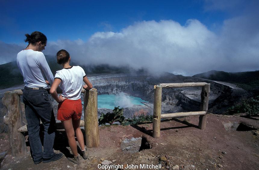 Young couple looking into the steaming crater of avtive Poas Volcano, Parque Nacional Volcan Poas, Costa Rica