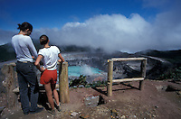 Young couple looking into the steaming crater of avtive Poas Volcano, Parque Nacional Volcan Poas, Costa Rica