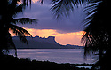 Sokehs Rock, lagoon and palm trees at sunset from the restaurant and bar at The Village Hotel; Pohnpei, Micronesia.