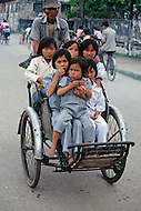 In Ho Chi Minh City, Saigon, February 1988. Street scene, the rickshaws replacing the children buses to bring them home after school.
