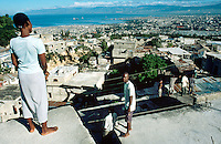 Haiti. Province of Ouest. View on Port-Au-Prince from the slum of Decayette (located in the area of Carrefour Feuille). Daily life for young people who are jobless. They have nothing to do. They just look at the huge and densely populated town they live in.  © 2003 Didier Ruef