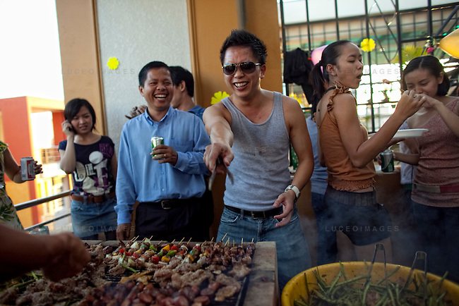 Phil Nguyen, middle, a Vietnamese-American businessman living in Vietnam, grills food during an office party in Ho Chi Minh City...Kevin German / LUCEO