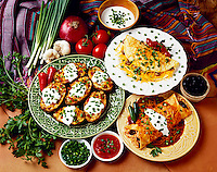 Prepared plates of enchiladas, twice baked potatoes and cheese omelet, all garnished with chopped green onions, studio.