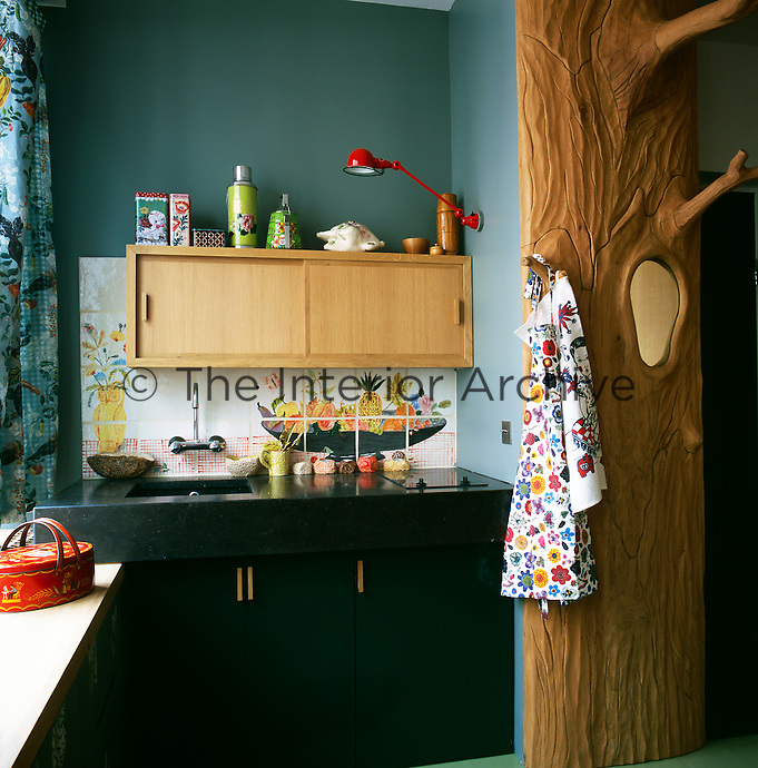 In the kitchen, decorative painted tiles provide a splashback behind the sink. Next to the units stands an interesting carved wood hat stand