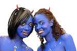 Two beautiful smiling girls with their skin painted in blue. Isolated portrait on white background.